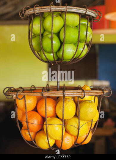 Baskets of green apples, Oranges, and lemons at NAM Restaurant at Bon Ton Resort. Langkawi, Malaysia - Stock Image