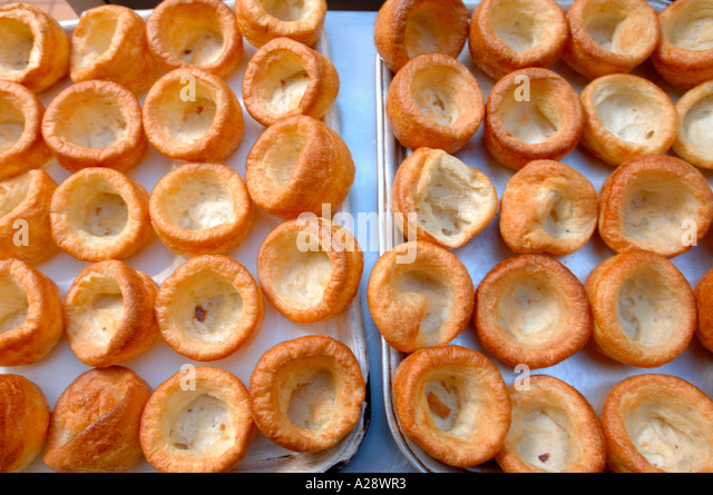 INDIVIDUAL YORKSHIRE PUDDINGS ON A BAKING TRAY FOR NEW HEALTHY SCHOOL DINNERS UK - Stock-Bilder