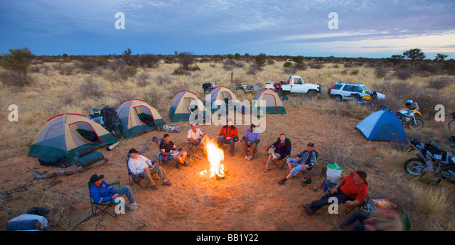 Bikers sit around a fire at camp, Central Kalahari Desert, Botswana - Stock Image