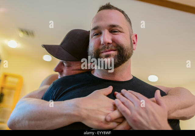 Close up of gay couple hugging - Stock Image