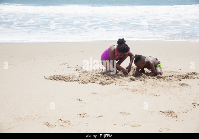 Children digging in sand on beach - Stock Image