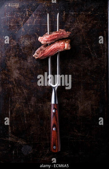 Slices of Rare beef steak on meat fork on dark background - Stock Image