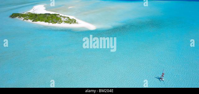 Catamaran sailing near a desert island, the Maldives, Indian Ocean - Stock Image