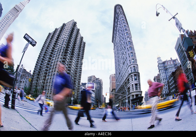 Commuting New York City Flatiron Building. several people unrecognizable from motion-blur - Stock Image