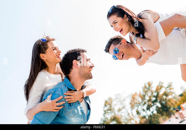 Group of young happy people carrying women on a sandy beach piggyback - Stock Image