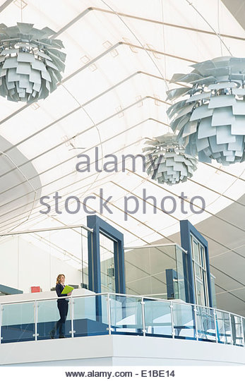Businesswoman on atrium balcony - Stock Image