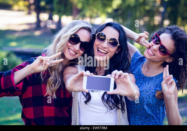 Happy hipsters taking a selfie in the park - Stock Image