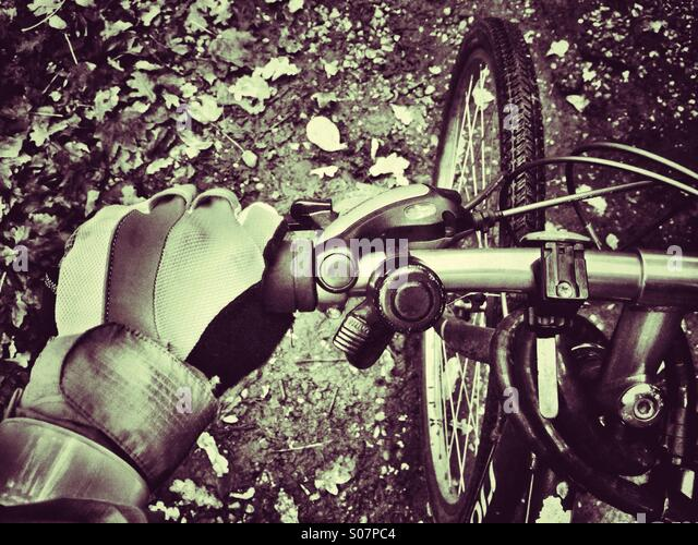 Detail of cyclist riding a muddy trail, showing left hand and handlebars in close-up - Stock Image