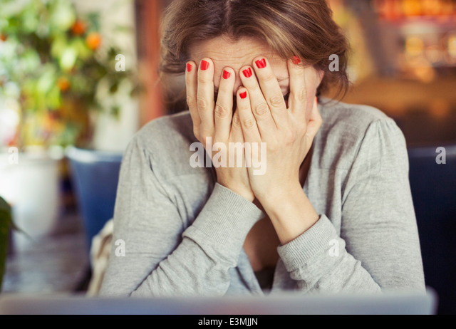 Sad young woman sitting with head in hands at home - Stock Image