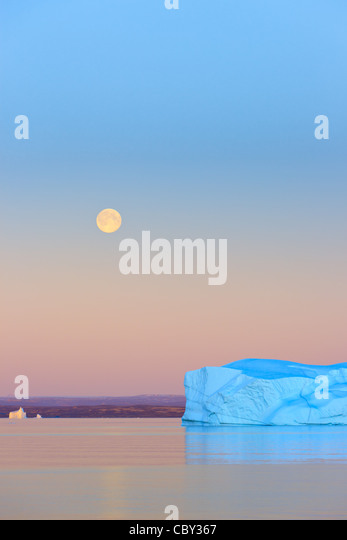 Iceberg at Sunset and Moonrise at Hall Bredning, Scoresbysund, Greenland - Stock Image