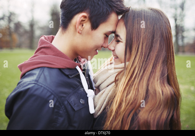 Close up of cute teenage couple in love sharing a special moment. Romantic young man and woman outdoors in park. - Stock-Bilder
