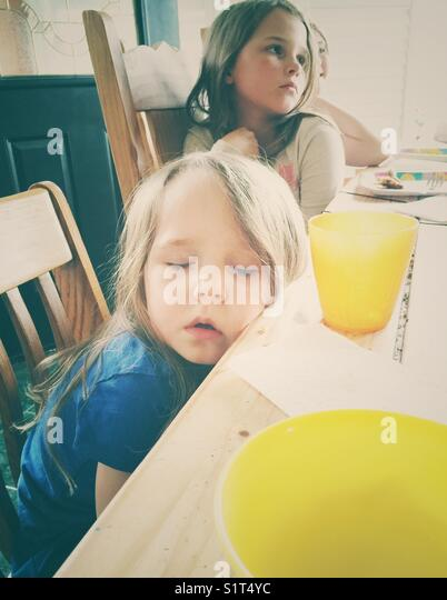 Toddler girl that has fallen asleep at the dining table with her sisters in the background - Stock Image