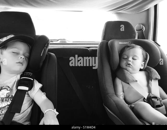 Preschooler and baby asleep in a car. - Stock Image