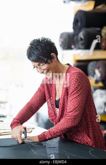 Mature seamstress using scissors to cut textile at work table - Stock Image