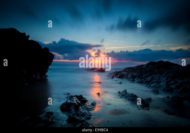 Cloudy sunset over the rocks along the Cornish coast near Newquay, Cornwall, England - Stock Image
