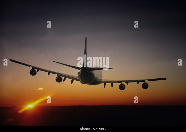 Plane Flying, sun setting on horizon, back view - Stock Image