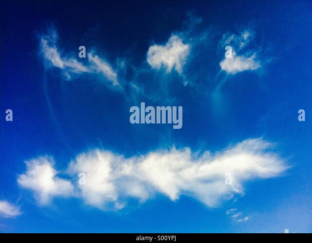 Strange looking clouds in blue sky - Stock Image