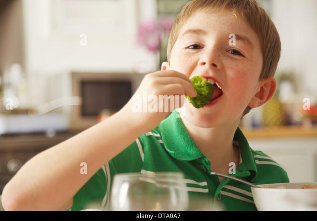 Young Boy Eating Broccoli - Stock Image
