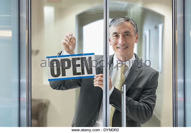 Chinese businessman hanging Open sign in window - Stock Image