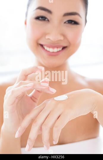 MODEL RELEASED. Young Asian woman applying cream to hand, portrait. - Stock-Bilder