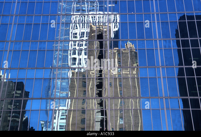 Window reflection of blue sky and tall buildings, New York City USA - Stock Image