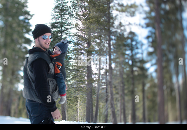 A father, age 35, walk with his son, age 4 months, in the snow covered wilderness of Lake Tahoe, Calfornia. - Stock Image