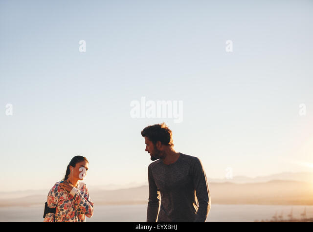 Shot of young couple of runners taking a rest after running training, Man and woman standing outdoors in morning - Stock Image