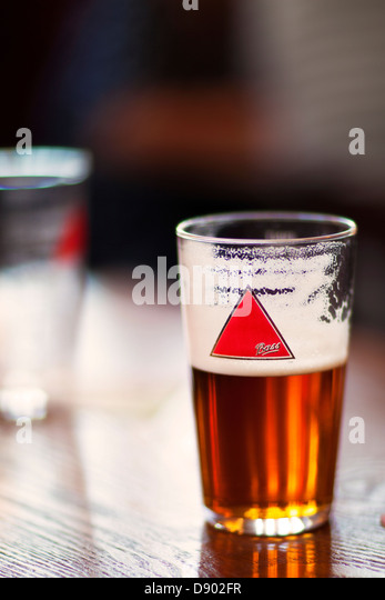 Glass half full...A half pint of Bass beer in a pint glass in a British pub on a wooden table - Stock Image