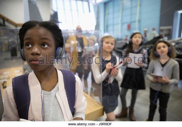 Curious African American girl student wearing headphones, looking at exhibit on field trip in war museum - Stock-Bilder