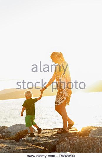 France, Provence-Alpes-Cote d´Azur, Saint Tropez, Woman walking with son along rocky coast at sunset - Stock Image