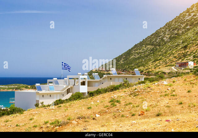 Modern Greek architecture, new white building in constructivist style, stands on shore of Cretan sea on roof mounted - Stock Image