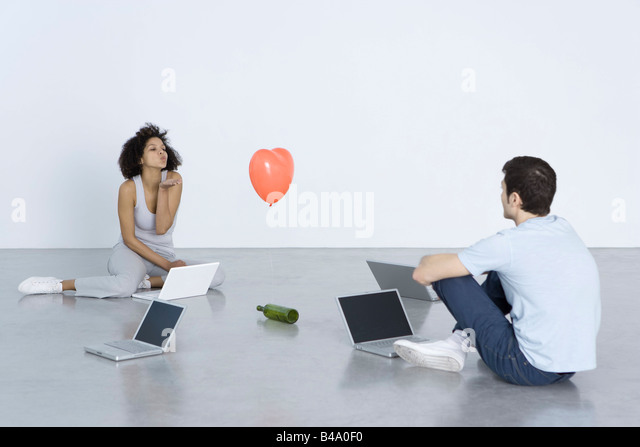 Man and woman seated with laptops, woman blowing man a kiss, bottle and heart balloon between them - Stock-Bilder