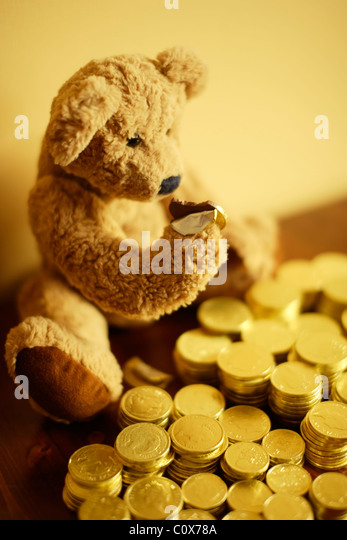 Ted tucks into his chocolate gold coin investment. - Stock-Bilder