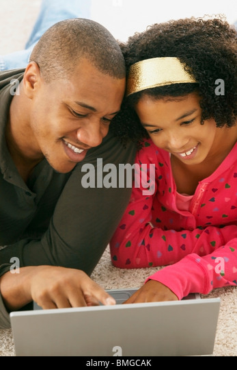 A Father And Daughter Working On A Laptop Computer - Stock Image