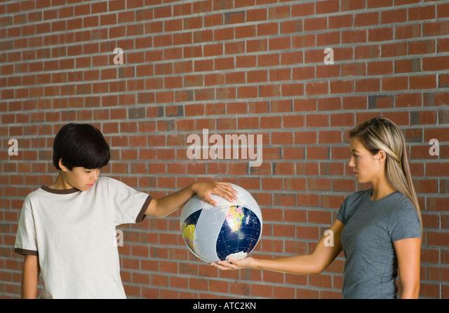 Boy and woman holding bandaged globe together - Stock Image