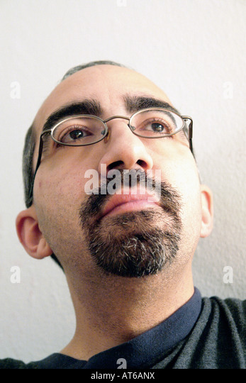 Portrait of a man of Hispanic Ethnicity.  He is wearing eyeglasses and is viewed from a low camera angle Copy Space - Stock Image