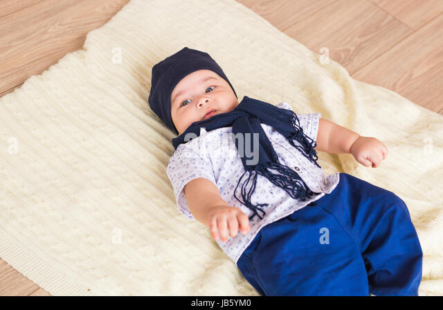Portrait of a little adorable newborn infant baby boy lying on back on blanket - Stock Image