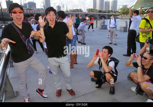 Singapore Singapore River Marina Bay Merlion Park Asian man posing imitating taking picture camera smart phone - Stock Image