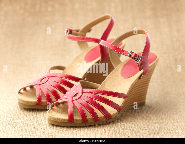 pair of red womens shoes sandals on a raffia background - Stock Image