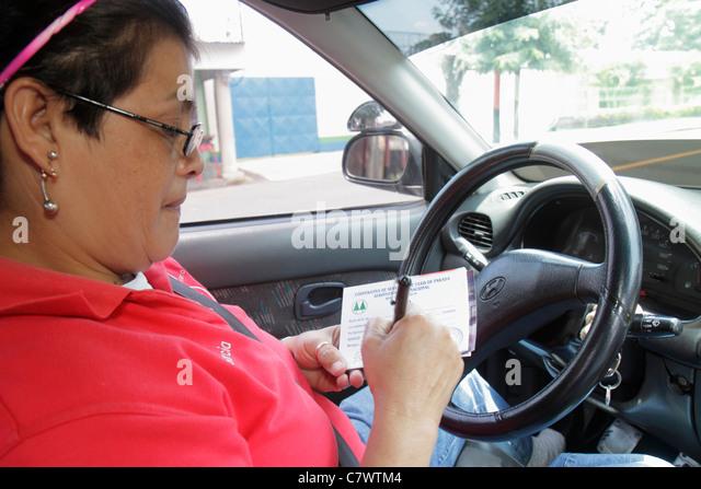 Nicaragua Managua taxi cab driver job Hispanic woman writing pen receipt eyeglasses steering wheel - Stock Image