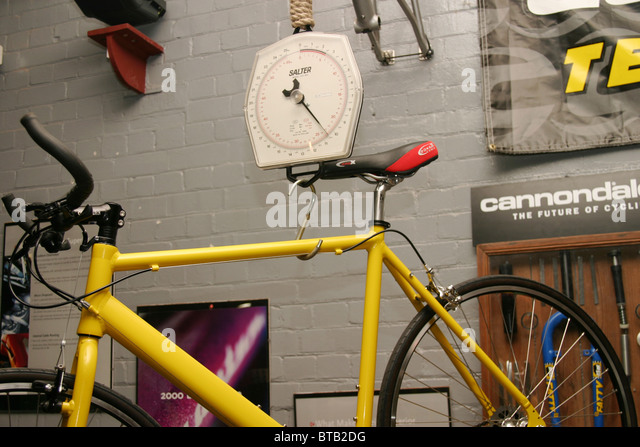 weighing a lightweight bike in a cycle workshop - Stock Image