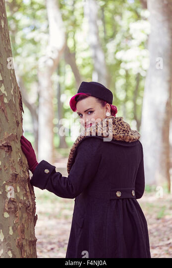 Portrait of fashionable young woman with coloured hair viewing over her shoulder in the woods - Stock Image