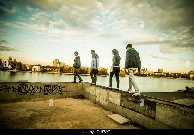 Four friends walking along concrete wall, Russia - Stock Image