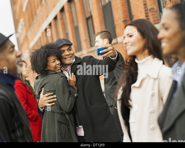 A man holding out a camera phone and taking pictures of the group Kissing a young woman Men and women - Stock-Bilder
