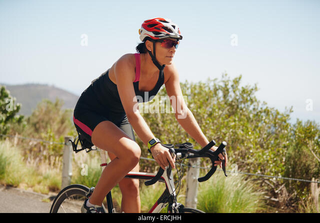 Young woman triathlon athlete cycling on country road. Woman riding bicycle practicing for triathlon competition. - Stock Image