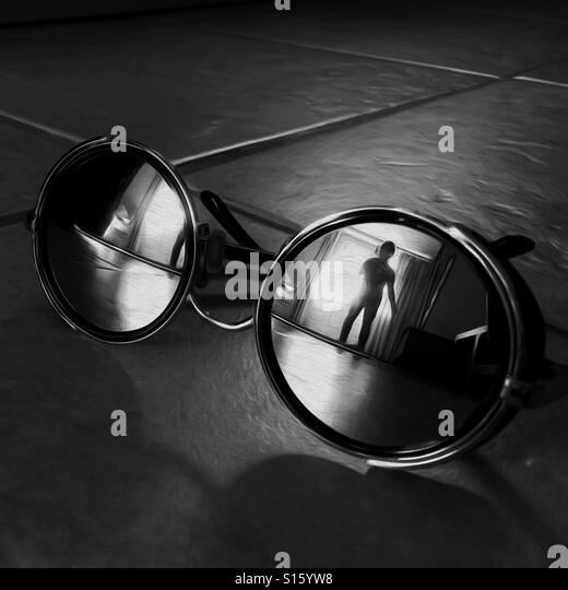 Intruder reflected in round mirrored sunglasses - Stock-Bilder