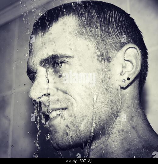 Happy guy in shower cooling down - Stock Image