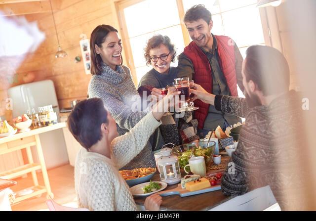 Friends toasting wine glasses at cabin table - Stock-Bilder