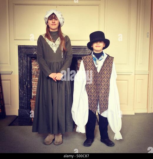 Brother and sister dressing up in old fashioned clothes - Stock Image