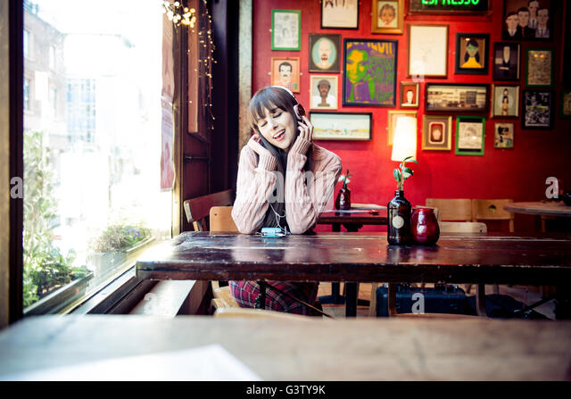 A young woman sitting at a table in a coffee shop in Manchester. - Stock-Bilder